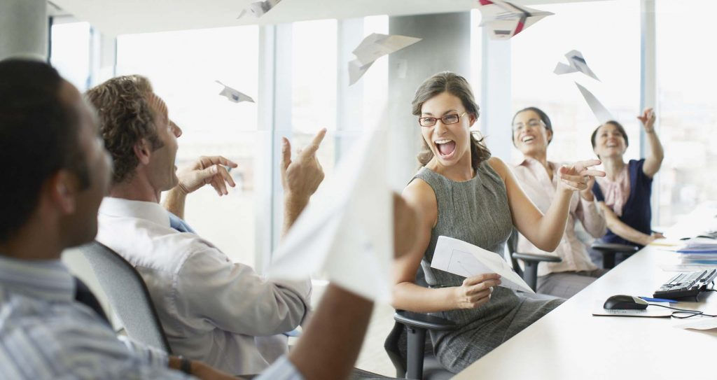 Businesspeople throwing paper airplanes in office