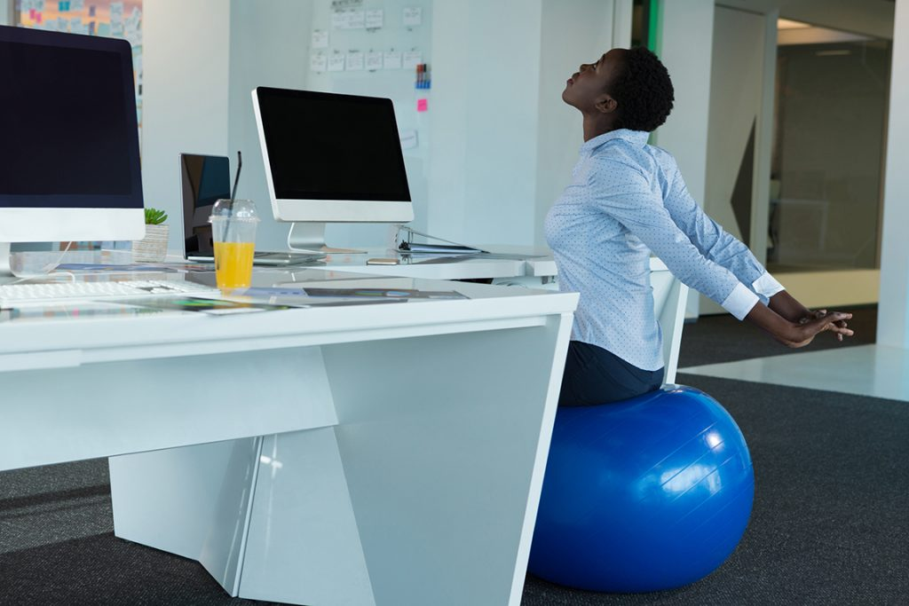 Executive exercising on fitness ball in futuristic office